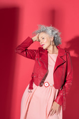 Woman wearing pink dress and red jacket posing for magazine