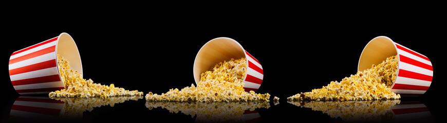 Set of paper striped buckets with scattered popcorn isolated on black background