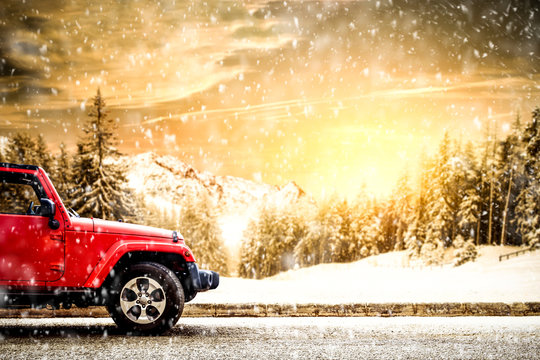 red winter car and snow flakes. Forest landscape and mountains.