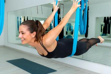 Fun portrait of girl doing aerial yoga in gym