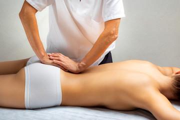 Physiotherapist applying pressure on lumbar spine.