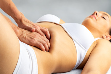 Physiotherapist applying pressure on woman's stomach