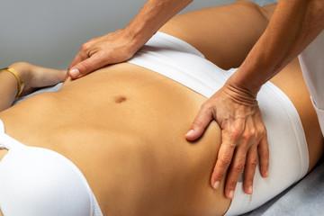 Physiotherapist manipulating female abdomen.