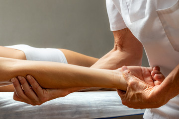 Physiotherapist manipulating wrist and elbow on woman.