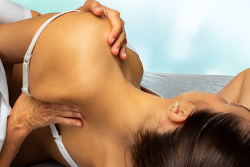 Therapist manipulating shoulder blade on young female patient
