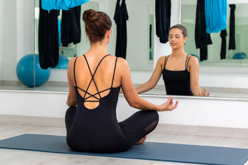 Woman meditating in gym with eyes closed