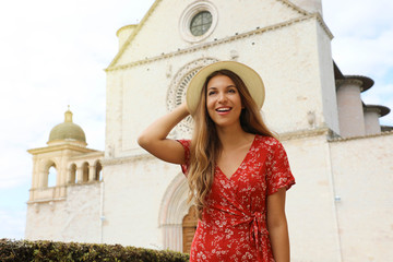 Portrait of beautiful woman in front of Assisi Basilica of Saint Francis. Travels in Italy.