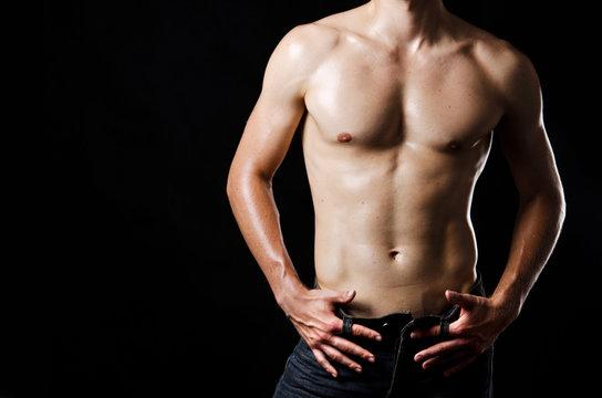 Slim muscular male torso at black background