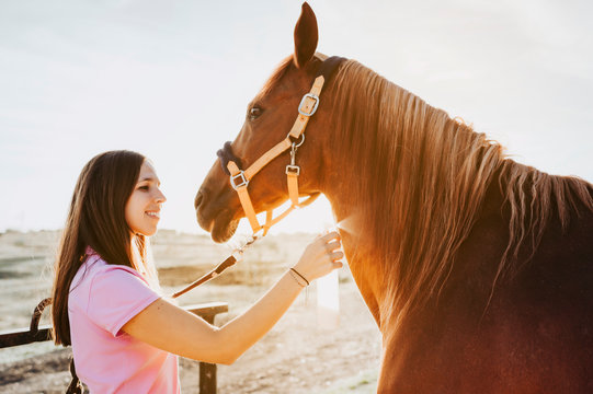 Side view of woman spraying skin of sorrel horse with special liquid while standing in light barn