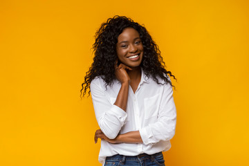 Happy smiling african american woman touching her neck