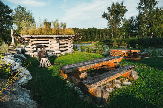 Small log houses for outdoor recreation are located on the river Bank. Hunting ground. Table of logs in the camping for tourists. Home and garden furniture. agrotourism