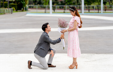 Man kneeling with bouquet to a woman in the park. Love, couple, relationship and engagement concept..