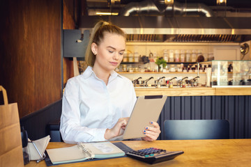 Mature small business owner calculating finance bills of activity – Female entrepreneur using digital tablet to pay invoice and taxes and to calculate financial expenses of new business start-up