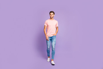 Full length body size view of his he nice attractive cheerful cheery content guy wearing pink tshirt strolling walking isolated on violet purple lilac pastel color background Wall mural