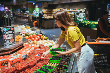 young woman taking berries from store shelf