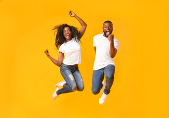 Joyful black couple jumping up and down Wall mural