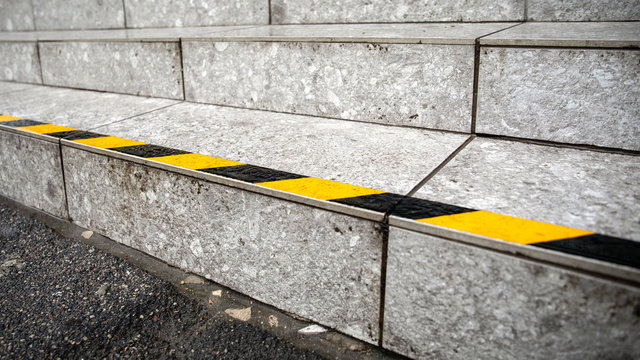 Yellow anti slip warning tape on stairs outdoors for safety. Public building