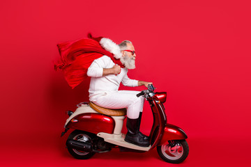 Profile side view of nice bearded gray-haired Saint Nicholas riding motor delivering carrying...