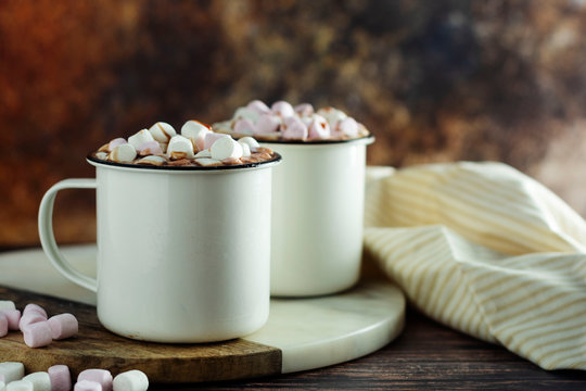 Two cups of hot chocolate, cocoa or warm drink with marshmallows on dark background