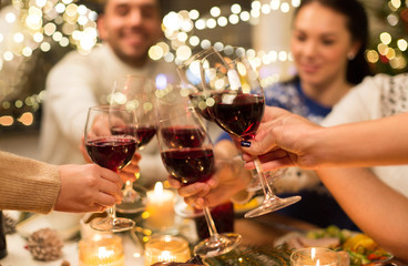 holidays and celebration concept - close up of happy friends having christmas dinner at home, drinking red wine and clinking glasses