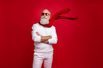 Trendy grey-haired superhero santa wear sun specs knitted clothes isolated red background