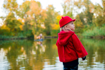 Little girl in the fall. Girl in a red coat near the pond.  Fashionable baby in a red coat for a walk.