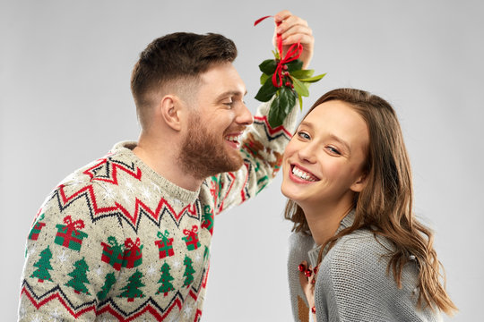 christmas, people and holiday traditions concept - portrait of happy couple in ugly sweaters kissing under the mistletoe over grey background