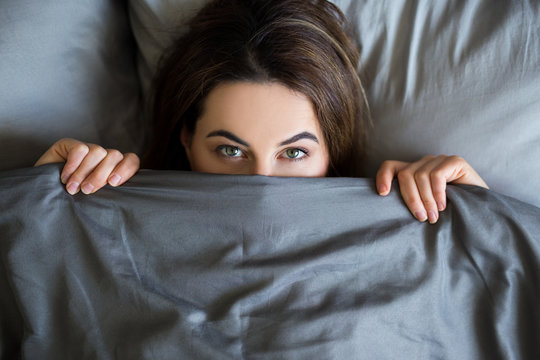 young beautiful woman lying in bed under blanket