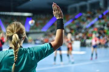Handball referee gives signal playing for time during handball match.