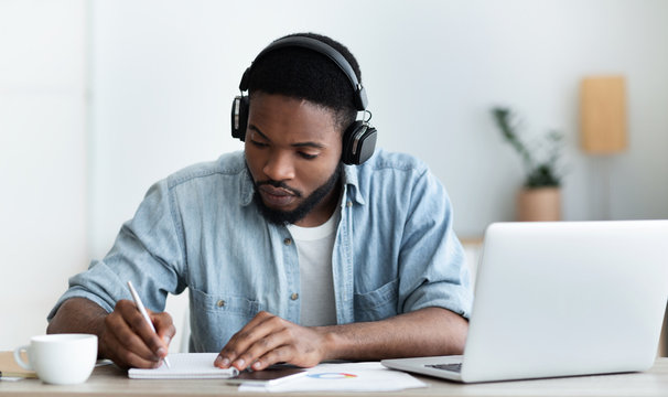 Serious african american student in headphones studying foreign language online