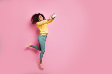 Travel motion lifestyle people modern technology concept. Full photo of cheerful carefree excited trendy style girl making self-portrait jumping wear yellow sweatshirt pants isolated pink background