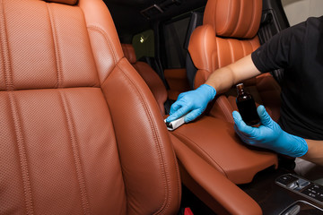 Applying a nano-ceramic coating on leather of the car seat brown upholstery by a worker in blue gloves with a sponge and bottle