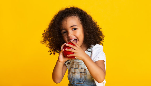 Vitamin snack. Little girl biting red apple
