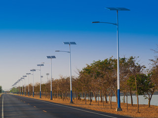 solar street light lamp post led with panel system on the road with green tree and blue sky for background energy saving concept.. Fotomurales