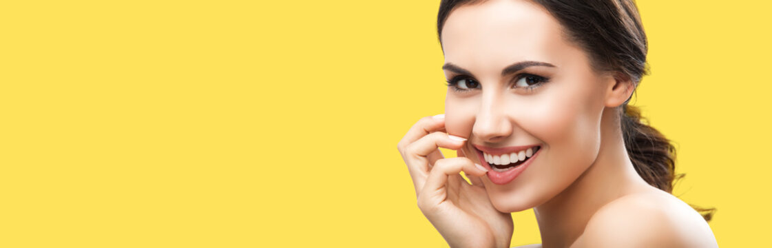 Portrait of beautiful young woman with naked shoulders, isolated over yellow color background, with copy space area, for some text, advertising or slogan. Brunette girl in studio picture.