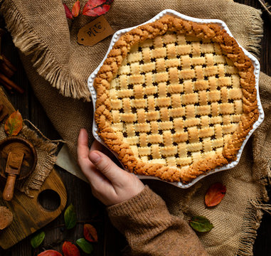 overhead shot of homemade thanksgiving warm baked apple lattice pie crust in woman hands on sackcloth on rustic wooden table with apples, spices, autumn leaves