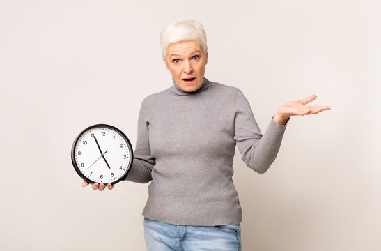 Shocked elderly woman holding wall clock and gesturing with hand