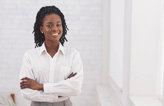 Smiling Afro Business Girl Standing Crossing Hands Against White Wall