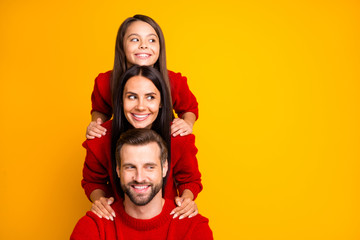Photo of cute cheerful funny funky family having created pyramid looking away at empty space smiling wearing red sweater toothily isolated over vivid color background