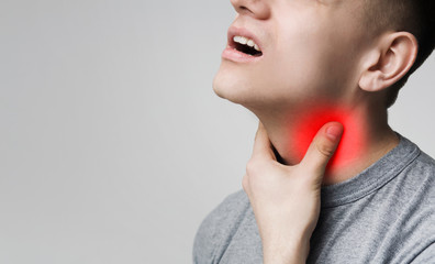 Man with thyroid gland problem, touching his neck
