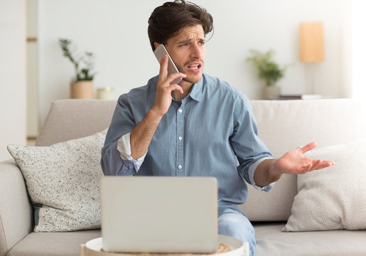 Unsatisfied Guy Complaining About Problems With Laptop By Phone Indoor