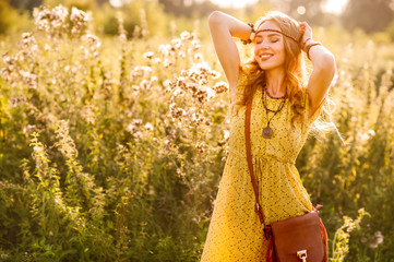 Smiling bohemian girl in yellow dress with guitar on the field at sunset warm light