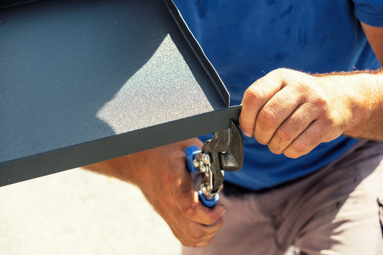 Worker cutting the sheet metal flashing with hands scissors