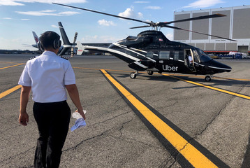 A pilot walks media members towards a helicopter operated by Uber Copter, a new service by the ride-sharing company Uber in New York