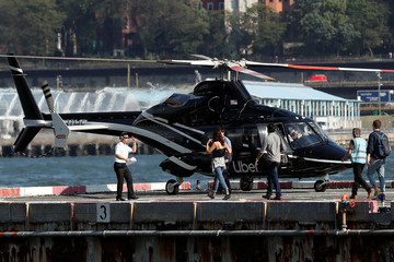 Passengers are escorted to a waiting helicopter operated by Uber Copter, a new service by the ride-sharing company Uber in New York