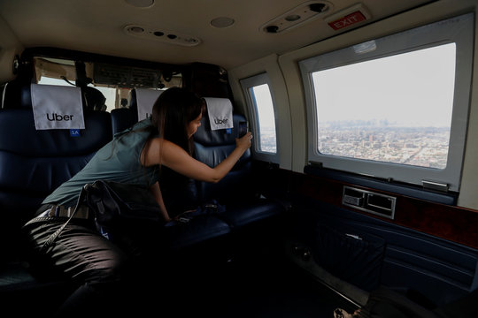 Media member takes picture from helicopter operated by Uber Copter, a new service by the ride-sharing company Uber, takes off from Manhattan in New York