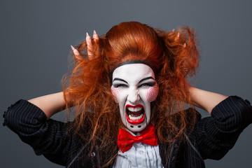 Red-haired girl with creative make-up and hairstyle for a Halloween party.