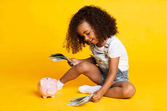 Little afro girl playing with money banknotes