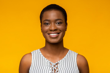 Portrait of smiling black woman on yellow background