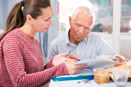 Sad young woman and father with financial documents at home